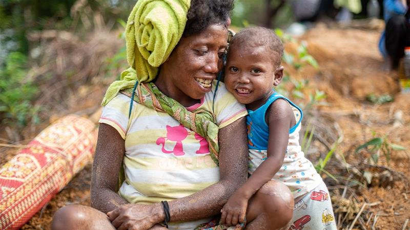 A mother with her child in the village of Kuala Koh [Chris Humphrey/Al Jazeera]
