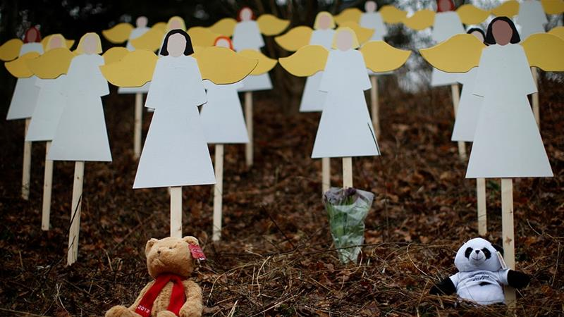 Stuffed animals left by mourners sit beneath some of the 27 wooden angel figures placed in a wooded area beside a road near the Sandy Hook Elementary School for the victims of a school shooting in Newtown, Connecticut [File: Mike Segar/Reuters]