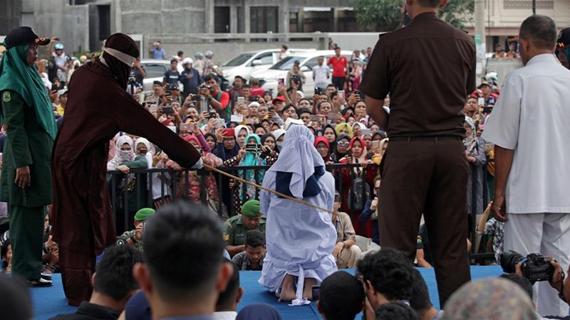 An Indonesian woman is caned in front of a crowd of onlookers after being found guilty of prostitution in Banda Aceh [File: Oviyandi Emnur/Reuters]