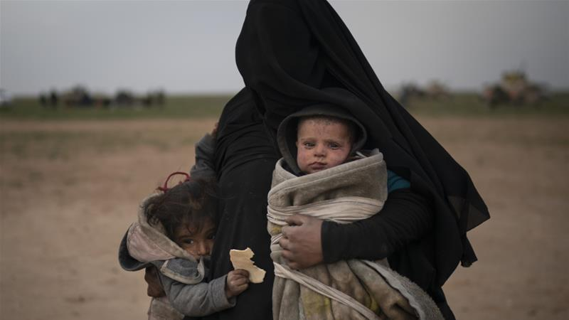A woman evacuated from the last territory held by ISIL militants carries two children after being screened by the SDF outside Baghouz, Syria on February 26, 2019 [File: AP/Felipe Dana]