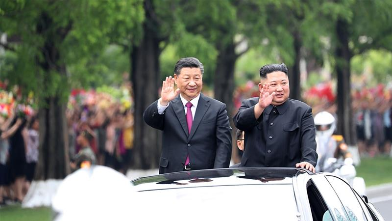 Xi and Kim wave from an open-top limousine as they travel along a street in Pyongyang [Ju Peng/Xinhua via AP Photo]