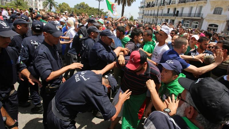 Police officers and demonstrators confront each other during a protest demanding the removal of the ruling elite in Algiers [Ramzi Boudina/Reuters]