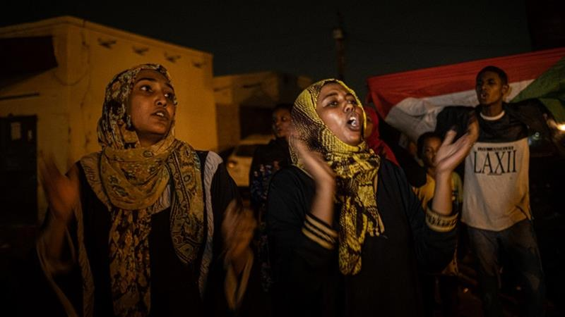 Sudanese protesters chant slogans demanding a civilian government at the barricades on a road in Omdurman [Yasuyoshi Chiba/AFP]