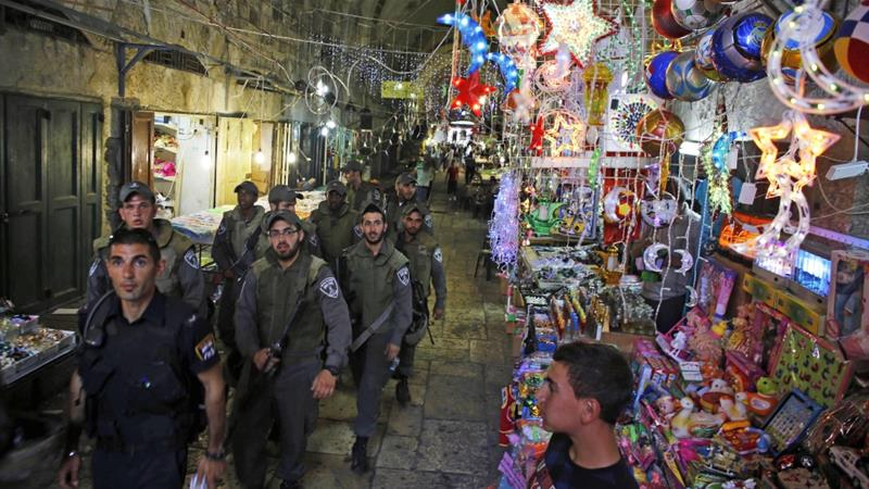 Israeli security forces pass by a shop selling decorations for the upcoming holy month of Ramadan as they patrol an alley in Jerusalem's Old City  on July 8, 2013 [File: Reuters/Ammar Awad]