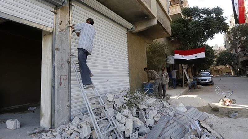 Workers rebuild destroyed shops in Harasta on the outskirts of Damascus in July 2018 [File: Louai Beshara/AFP]