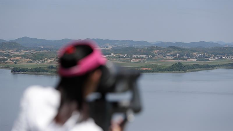 A woman looks at North Korea through binoculars from the unification observatory in Paju, South Korea on Sunday [Lee Jin-man/AP Photo]