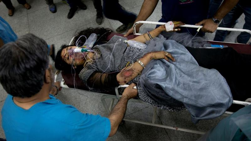 An injured female passenger of the minibus carried on a stretcher for treatment at a hospital in Srinagar [Dar Yasin/AP]