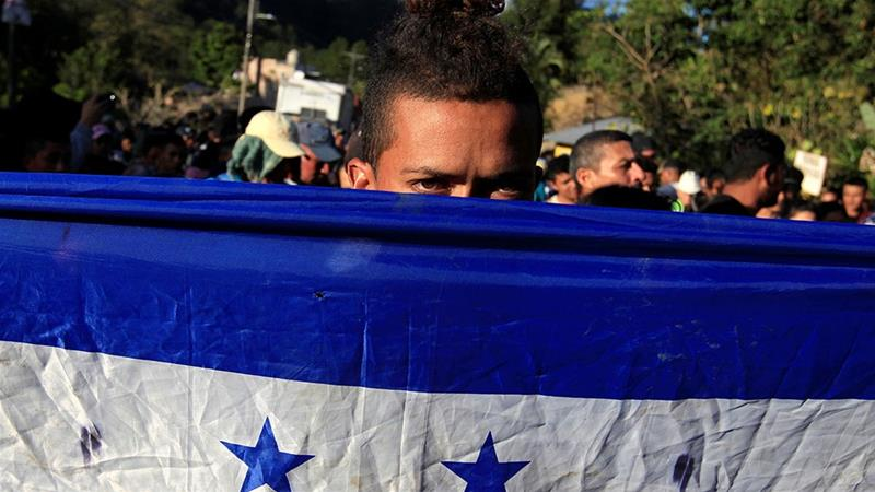 A Honduran, part of a new caravan of migrants traveling to the United States, looks from behind a Honduras flag as he waits to cross into Guatemala at the Agua Caliente border checkpoint in the municipality of Ocotepeque, Honduras [File: Jorge Cabrera/Reuters]