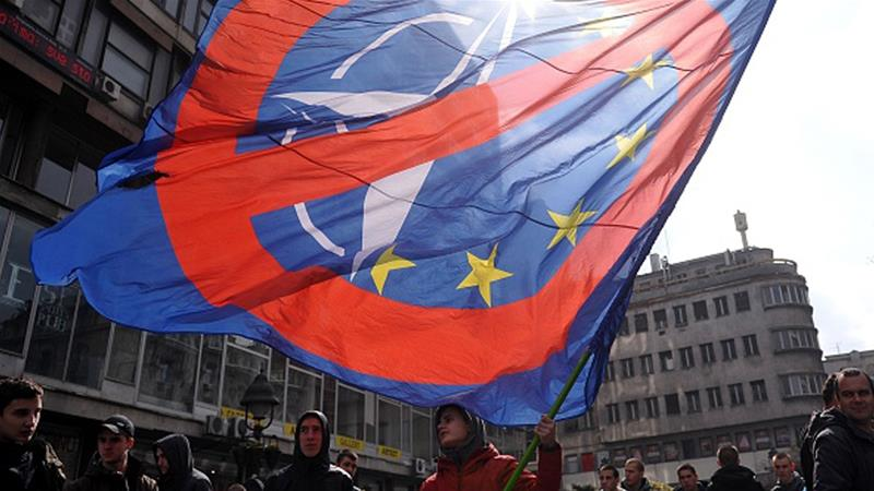A man waves a flag during an anti-NATO demonstration in Belgrade, Serbia in March 2016 [Alexa Stankovic/AFP/Getty Images]