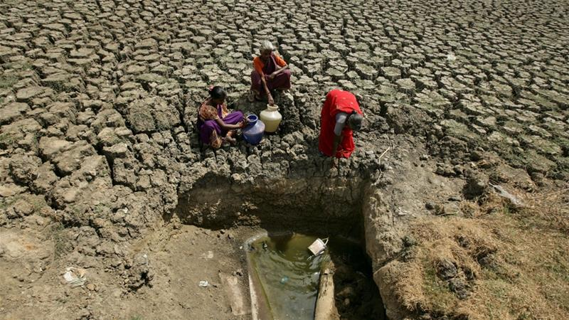 Women fetch water from an opening dug by residents at a dried-up lake near Chennai city [P Ravikumar/Reuters]