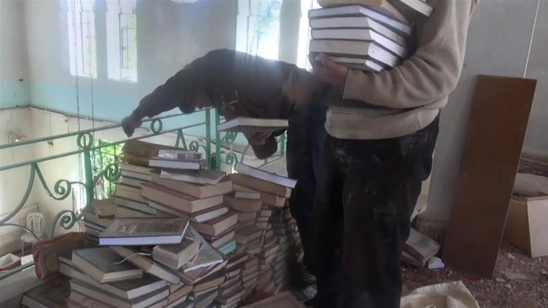 A group of friends save books from bombed-out buildings in Daraya, a suburb of Damascus [Al Jazeera]