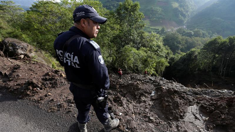 A police officer looks for victims after a mudslide in the Mexican town of Cuacuila [Henry Romero/Reuters]