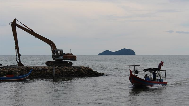 A fishing boat returns from the sea off the southern coast of the Malaysian island of Penang. The area, next to the airport, is the site for an ambitious plan to create three artificial islands [Kate Mayberry/Al Jazeera]