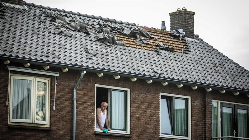 A damaged roof of a residential home after a possible tornado in Rheden, the Netherlands. The strong thunderstorms have caused damage throughout the country [Roland Heitink/EPA]