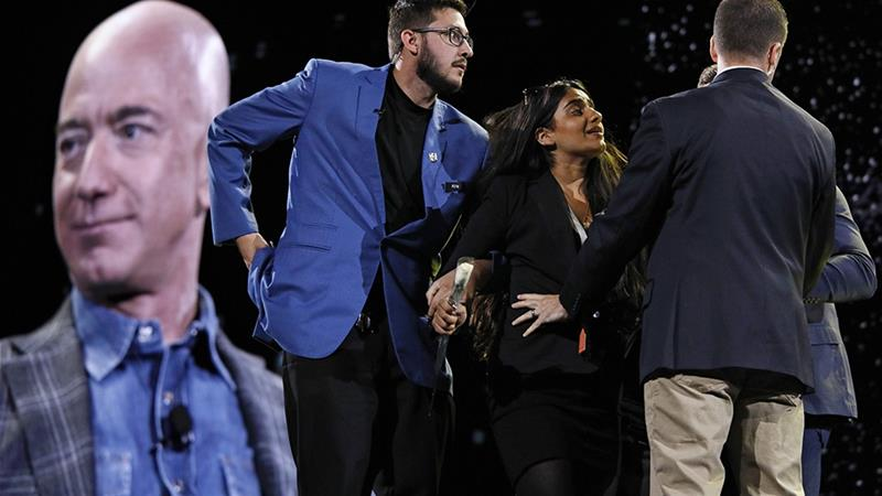 Security removes a protester, second from right, from the stage as Amazon CEO Jeff Bezos speaks at the the Amazon re:MARS convention in Las Vegas [John Locher/Associated Press]