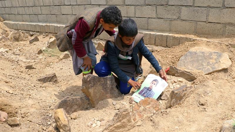 Children place a poster on the grave of a child killed in an air attack by the Saudi-led coalition on a bus in Saada, Yemen, in August 2018 [File: Naif Rahma/Reuters]