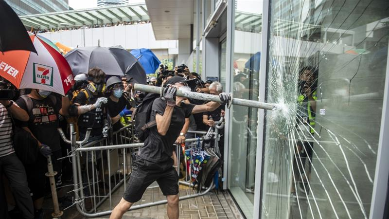 A protester is seen holding a steel pipe trying to break the glass outside the Legislative Council building [Vernon Yuen/NurPhoto via Getty Images]