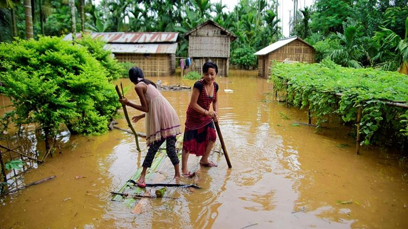 Girls row a makeshift raft past submerged houses at a flood-affected village in Karbi Anglong district in Assam [Anuwar Hazarika/Reuters]
