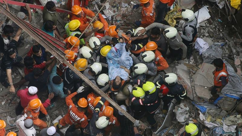 Rescuers carry a survivor from the site of a building that collapsed in Mumbai, India [Rajanish Kakade/AP]