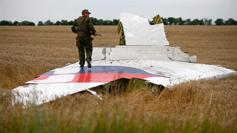 An armed pro-Russian separatist stands on part of the wreckage of the plane after it crashed near the settlement of Grabovo in the Donetsk region on July 17, 2014 [Maxim Zmeyev/Reuters]