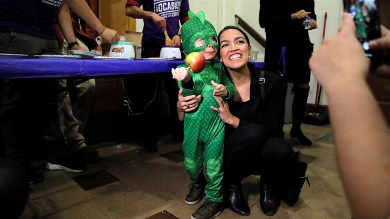 Representative Alexandria Ocasio-Cortez poses with a child at a political event in her native Parkchester section of the Bronx [Andrew Kelly/Reuters]