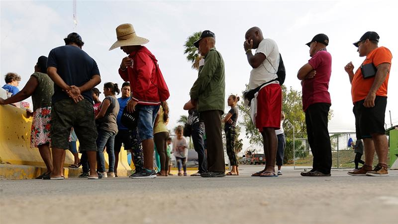 Migrants seeking asylum in the United States stand in line to receive breakfast from a group of volunteers near the international bridge in Matamoros, Mexico [File: Eric Gay/AP Photo]