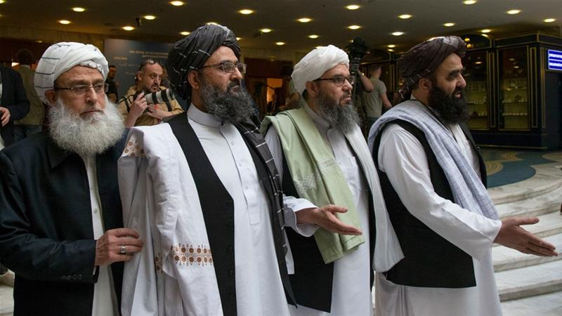 Mullah Abdul Ghani Baradar, the Taliban group's top political leader, second from left, arrives with other members of the Taliban delegation for talks in Moscow [File: Alexander Zemlianichenko/AP Photo]