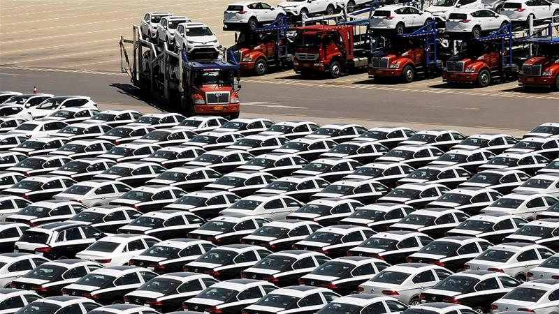 China has promised to open more of its economy to foreign investors as the world begins to feel the effect of the China-US trade dispute; here, a truck transports newly-manufactured cars at a port in Dalian in China [File: Reuters]
