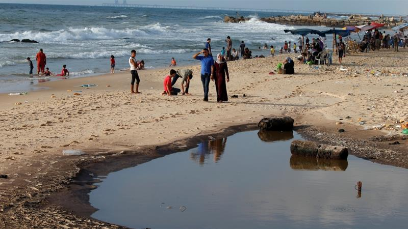 Palestinians walk past a pool of sewage on a beach in the northern Gaza Strip July 13, 2018 [File:Mohammed Salem/Reuters]
