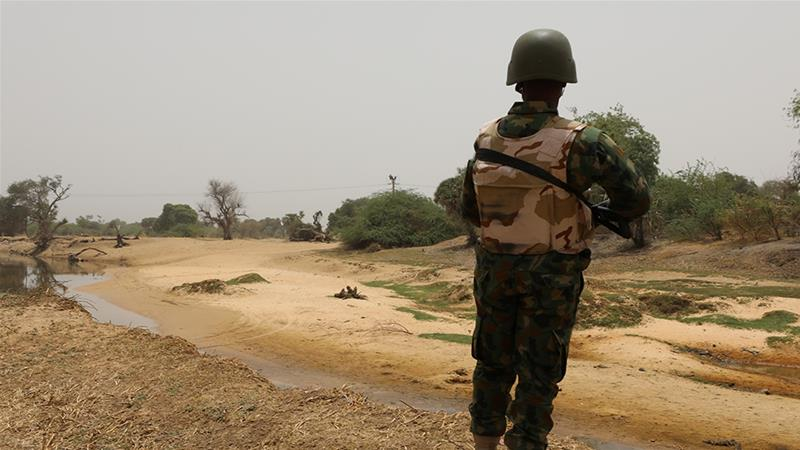 In this file photo, a Nigerian soldier stands watching the border with Niger at Damasak, Borno [File: Afolabi Sotunde/Reuters]