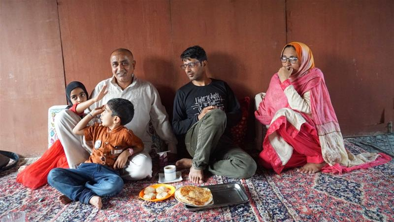 Ali Muhammad Bhat with his family members at his home in Indian-administered Kashmir's Srinagar city [Rifat Fareed/Al Jazeera]