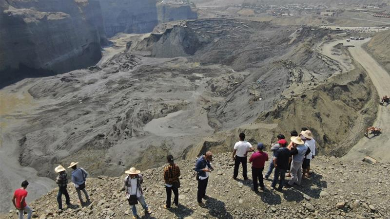 People stand atop a ridge overlooking the scene of a mudslide at a jade mine that killed 50 people in April [File: Zaw Moe Htet/AP]