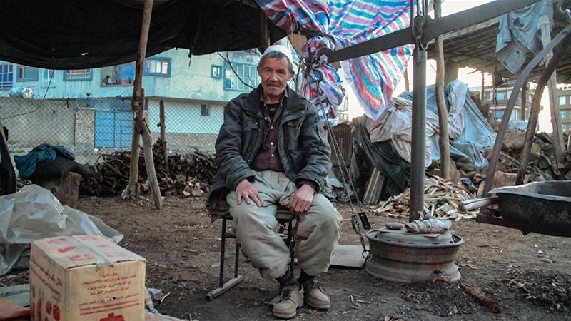 Asef, a wood seller, pictured at his stand in the Pur-e-Surkh district of Kabul [Agnieszka Pikulicka-Wilczewska/Al Jazeera]