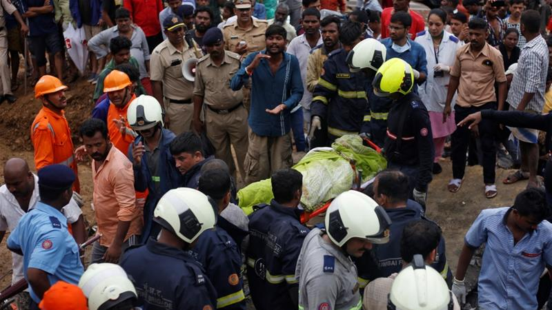 Rescue workers carry the body of a victim after a wall collapsed at a slum in Mumbai, India [Francis Mascarenhas/Reuters]