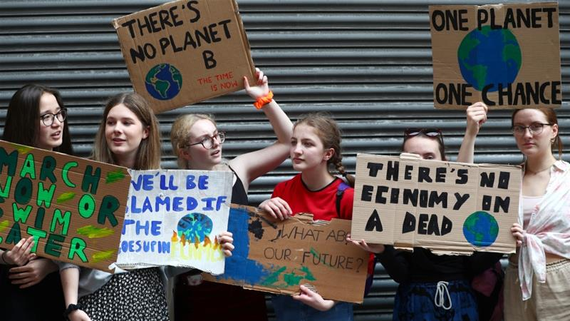 Protesters hold placards at a climate change demonstration in London, UK, on June 26, 2019 [Hannah McKay/Reuters]