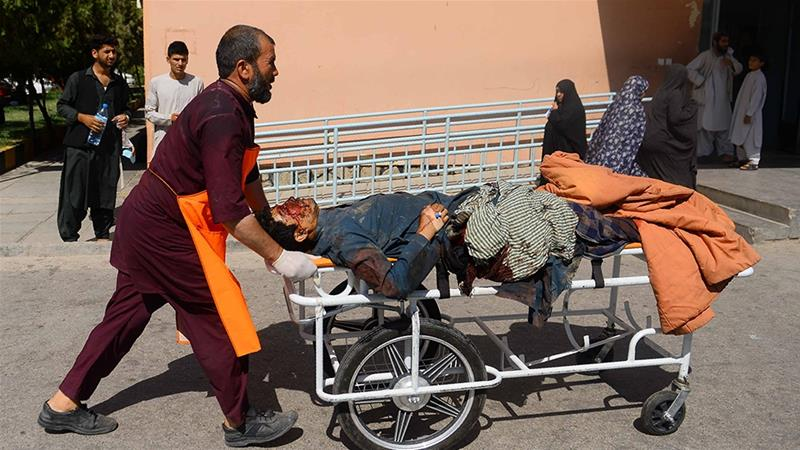 A wounded person is transported on a stretcher after the bus hit a roadside bomb [Hoshang Hashimi/AFP]