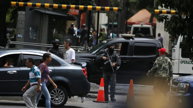 Masked agents of Venezuela's police intelligence agency stand guard in Caracas [Fernando Llano/AP]