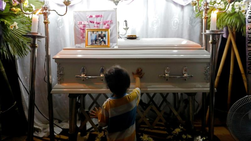 Brother of three-year-old Myka Ulpina stands by his sister's coffin. Myka is among the latest victims, having been shot during a police raid last weekend [Eloisa Lopez/Reuters]