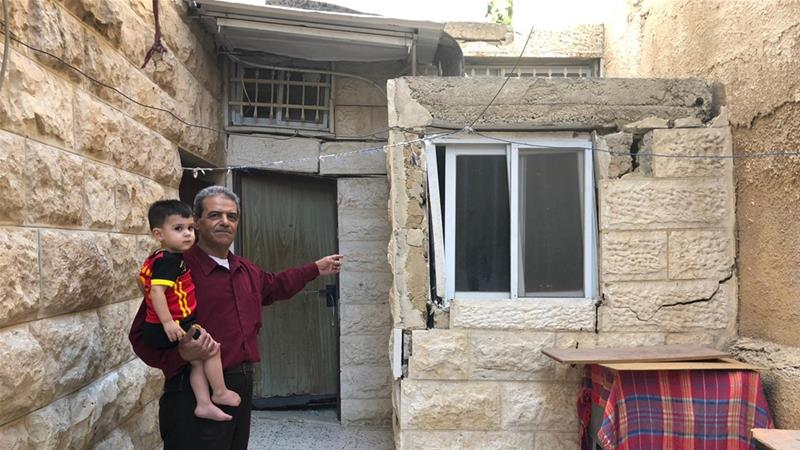Fayyad Abu Rmeleh shows the cracks and deformations that have formed in his home from Israeli excavations [Dareen Jubeh/Al Jazeera]