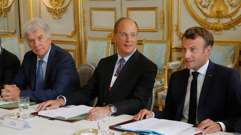 Yves Perrier, CEO of Amundi, left, and Larry Fink, chair and CEO of BlackRock, centre, meet with French President Emmanuel Macron during a gathering of investment-fund representatives discussing climate change [Michel Euler/Reuters]