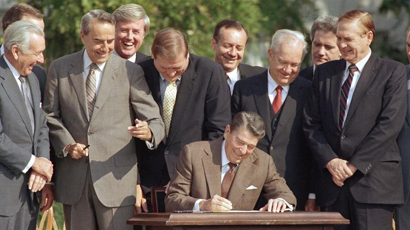 Congresspeople watch closely as President Ronald Reagan signs into law a landmark tax overhaul on the South Lawn of the White House in Washington, DC, on October 22, 1986 [File: Bob Daugherty/AP]