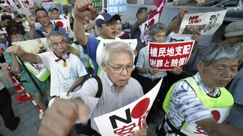 Protesters in Japan urged Prime Minister Shinzo Abe last week to reverse its recent decision against South Korea [Eugene Hoshiko/AP]