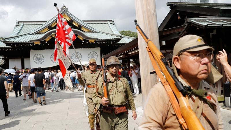 Men wearing Japanese imperial military uniform visit the Yasukuni shrine in Tokyo on Thursday [Kim Kyung-Hoon/Reuters]