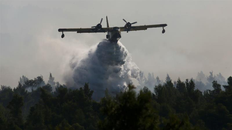 EU firefighting planes have been dropping tonnes of water over wildfires on the Greek island of Evia [Costas Baltas/Reuters]