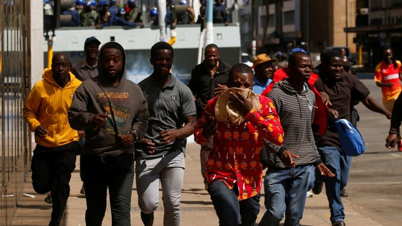 Protesters flee teargas during clashes after police banned planned rallies over austerity and rising living costs called by the opposition in Harare, Zimbabwe, on August 16 [Philimon Bulawayo/Reuters]