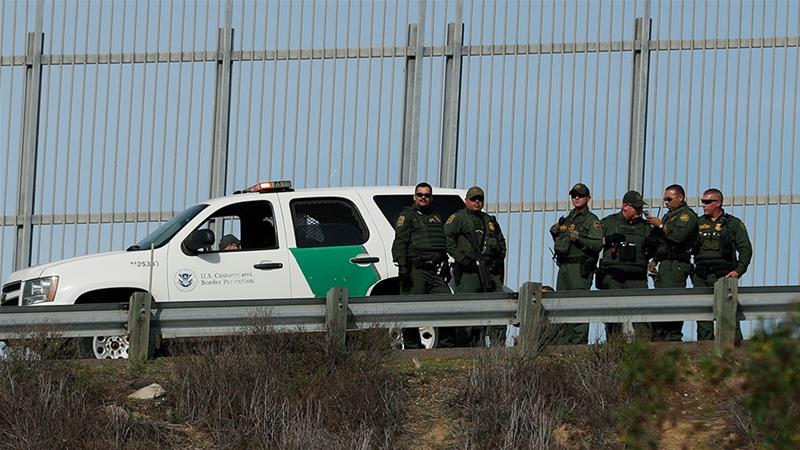 US Border Patrol agents stand in front of a secondary fence in San Diego, California looking across border wall towards Mexico [File: Rebecca Blackwell/AP Photo]