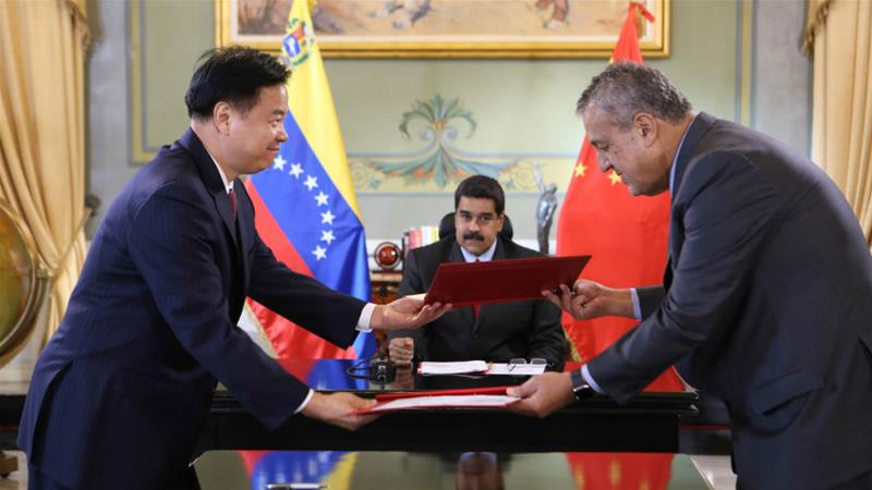 In 2016, Venezuela's President Nicolas Maduro, centre, looked on while CNPC's Wang Yilin, left, and Venezuelan oil minister Eulogio del Pino signed an agreement in Caracas [File: Miraflores Palace/Handout/Reuters]