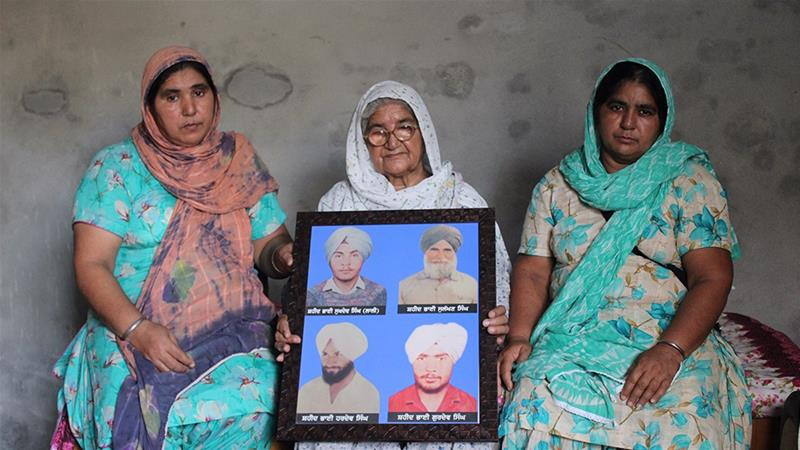 Gurmej Kaur holds an image of her husband and sons who died in the 1980s, at the height of tensions in Punjab as calls for a separate Sikh state led to a bloody crackdown [Bilal Kuchay/Al Jazeera]