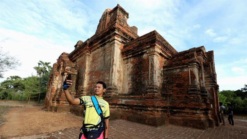 A cyclist takes a selfie with an ancient pagoda to celebrate Bagan being named as a UNESCO World Heritage Site in Bagan, Myanmar, July 27, 2019 [Ann Wang/Reuters]