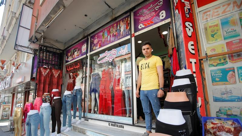A Syrian shopkeeper stands in front of his clothes shop in Istanbul's Kucukcekmece district [File: Kemal Aslan/Reuters]